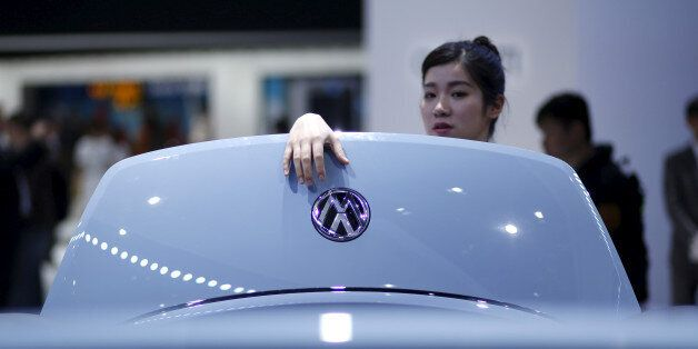 A woman looks a Volkswagen car during a presentation at the 16th Shanghai International Automobile Industry...