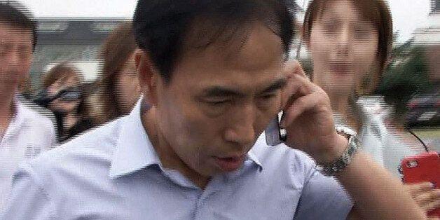 김수창 전 제주지검장이 2014년 8월 제주지검장 관사를 나오다 취재진에게 질문을 받고 있다. 공연음란 혐의를 받자 사임한 김 전 지검장은 이날 관사에 짐을 싸러 왔던 것으로