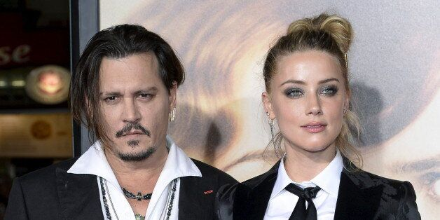 Cast member Amber Heard and husband Johnny Depp pose during the premiere of the
