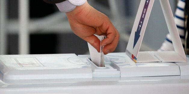 A man casts his ballot for the parliamentary election at a polling station in Seoul, South Korea, April...