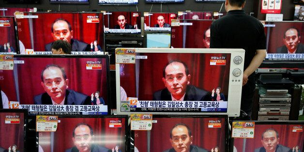 A sales assistant watches TV sets broadcasting a news report on Thae Yong Ho, North Korea's deputy ambassador...