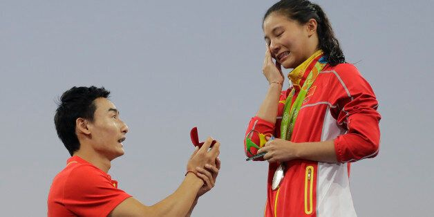 China's diver Qin Kai, left, proposes to silver medalist He Zhi of the women's 3-meter springboard diving...