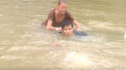 세 명의 남자가 홍수로 물에 잠긴 차에서 여성과 반려견을