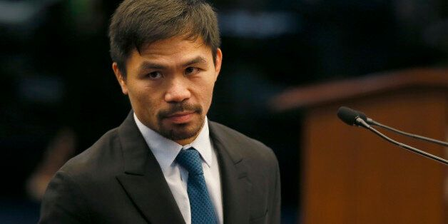 Filipino boxer and now Senator Manny Pacquiao listens to an interpellation by a fellow senator shortly...