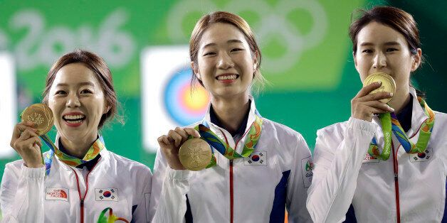 From left, South Korea's Chang Hye-jin, Choi Mi-sun and Ki Bo-bae shows their gold medals to photographers...