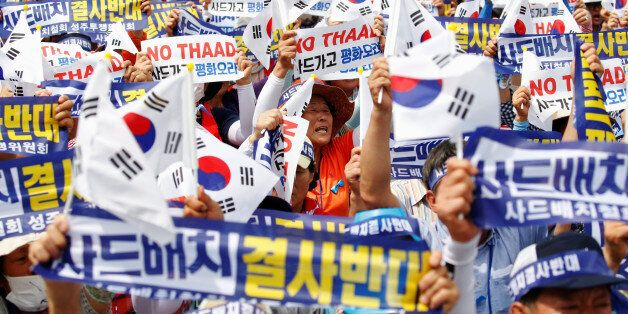 Seoungju residents chant slogans during a protest against the government's decision on deploying a U.S....