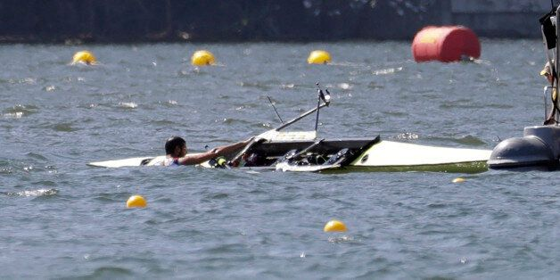 Milos Vasic and Nenad Bedik, of Serbia, are helped out of the water after capsizing while competing in...