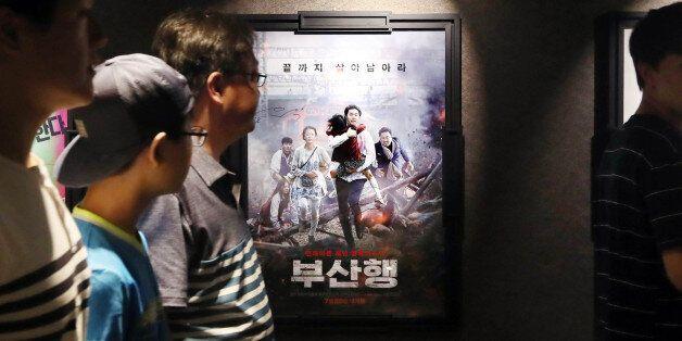 7일 오후 서울 강남구 한 멀티플렉스 영화관을 찾은 관객들이 '부산행' 포스터 앞을 지나고