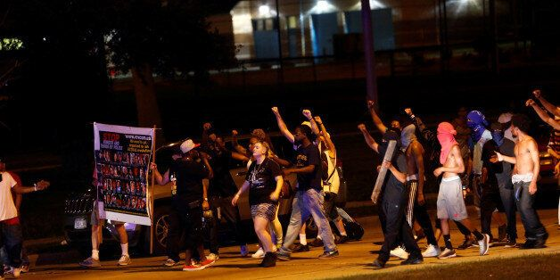 Protestors march toward police lines during disturbances following the police shooting of a man in Milwaukee,...