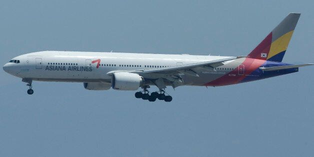 FILE - In this Tuesday, July 9, 2013 file photo, Asiana Flight 214 comes in for a landing over the wreckage...
