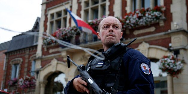 A policeman secures a position in front of the city hall after two assailants had taken five people hostage...