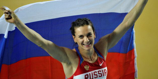 Gold medalist Elena Isinbayeva of Russia holds her national flag after the women's pole vault final during...