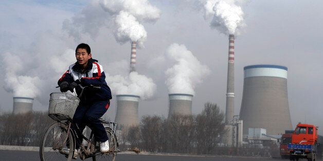 A Chinese boy cycles past a cooling towers of a coal-fired power plant in Dadong, Shanxi province, China,...