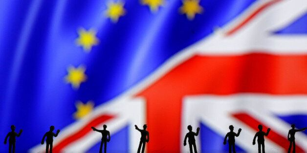 Miniature models of people are pictured in front of the European Union and UK flags in this photo illustration...