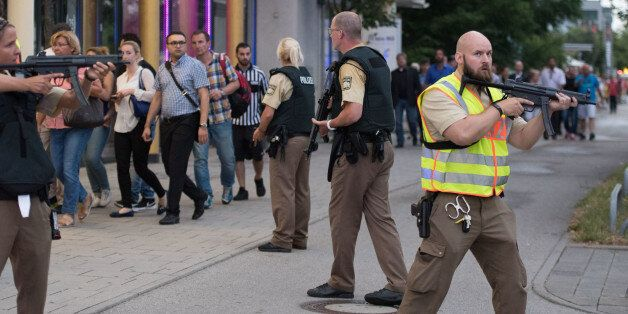 Police escort people who leave the Olympia mall in Munich, southern Germany, Friday, July 22, 2016 after...