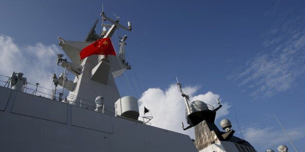 A Chinese People's Liberation Army (PLA) navy personnel looks out of their Jiangkai II class vessel,...