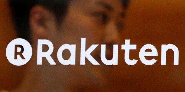 A staff of Rakuten Cafe is seen behind a logo of Rakuten Inc. at a shopping district in Tokyo August...