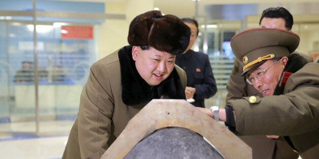 FILE PHOTO: North Korean leader Kim Jong Un looks at a rocket warhead tip after a simulated test of atmospheric...