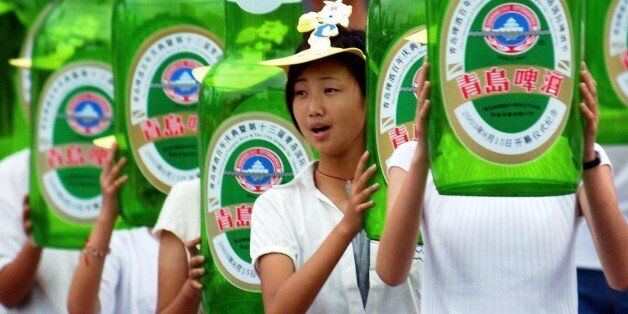 Young people hold balloon beer bottles of Tsingtao Beer during the opening ceremony of the 13th Qingdao...
