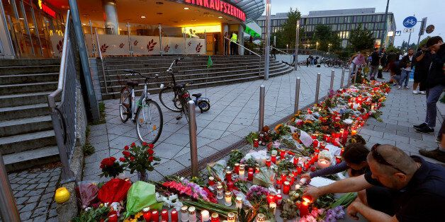 People light candles beside flowers laid in front of the Olympia shopping mall, where yesterday's shooting...