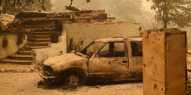 A burned car rests in front of a Palo Colorado area residence leveled by the Soberanes Fire near Big...