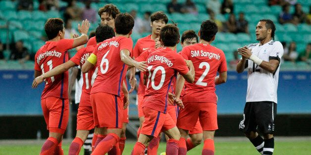 Players of Korea celebrate after scoring during a group C match of the men's Olympic football tournament...