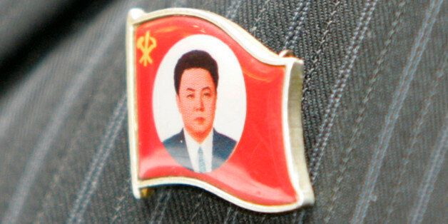 A North Korean labour union leader wears an insignia representing North Korean leader Kim Jong-il during...