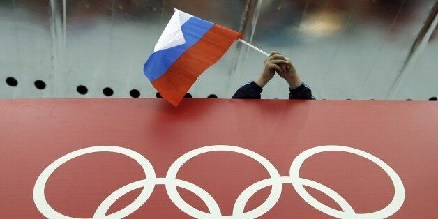 FILE - In this Feb. 18, 2014 file photo, a Russian skating fan holds the country's national flag over...