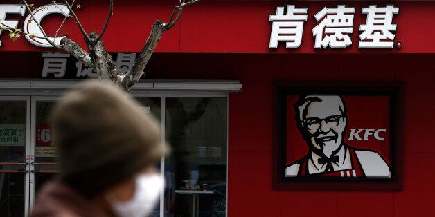 A woman, wearing a mask, rides past a KFC restaurant in Shanghai April 11, 2013. Yum Brands Inc, the...