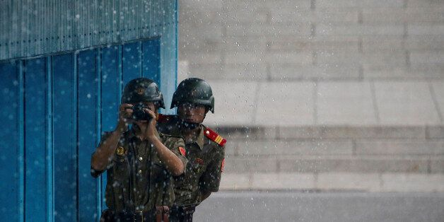 North Korean soldiers keeps watch toward the south as it rains during a ceremony marking the 63rd anniversary...