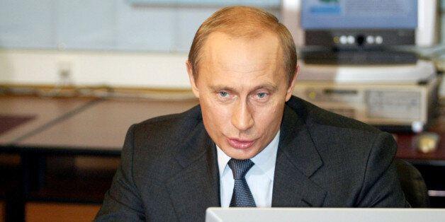 Russian President Vladimir Putin sits at a desktop computer in Moscow's Kremlin, January 19, 2004. Putin...