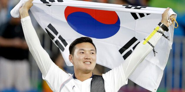 South Korea's Ku Bon-chan holds a National flag after winning the gold medals of the men's team archery...