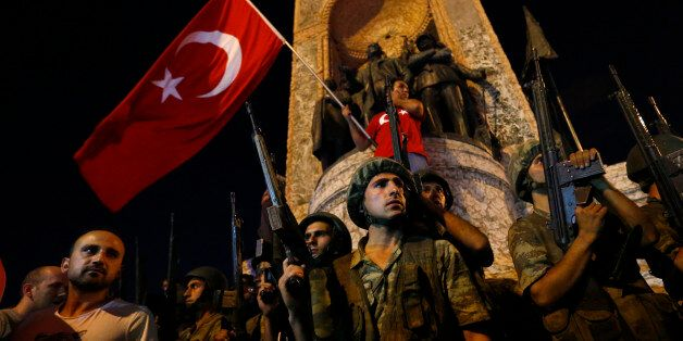 Turkish military stand guard near the the Taksim Square as people wave with Turkish flags in Istanbul,...