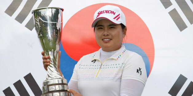 Park In-bee of South Korea holds her trophy in front of the national flag, after winning the Evian Masters...
