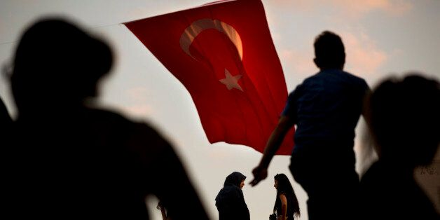 People walk by a Turkish flag in central Istanbul, Monday, July 18, 2016. Turkey's Interior Ministry...