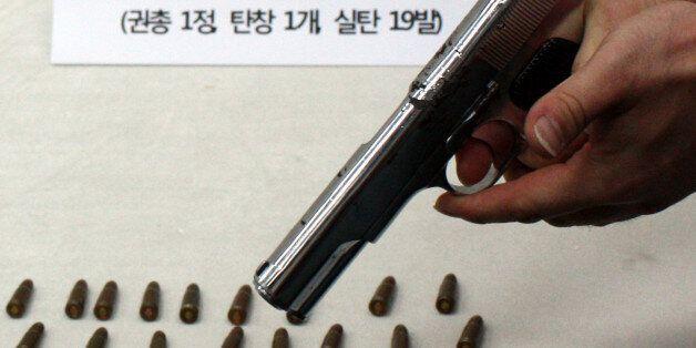 부산경찰청 마약수사대가 부산으로 잠입한 일본 조직폭력단(야쿠자) 조직원에게서 압수한 권총과 실탄. 경찰이 19일 방아쇠를 당겨 격발을 시연하고