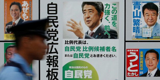 A police officer walks past Japan's ruling Liberal Democratic Party's (LDP) poster (2nd R) for the July...