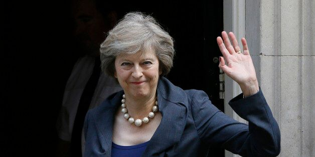 Britain's Home Secretary Theresa May waves towards the media as she arrives to attend a cabinet meeting...