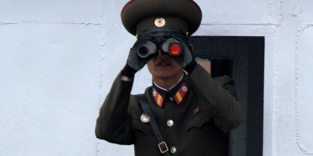 A North Korean soldier looks through binoculars on the Yalu River in Sinuiju, opposite the Chinese border...