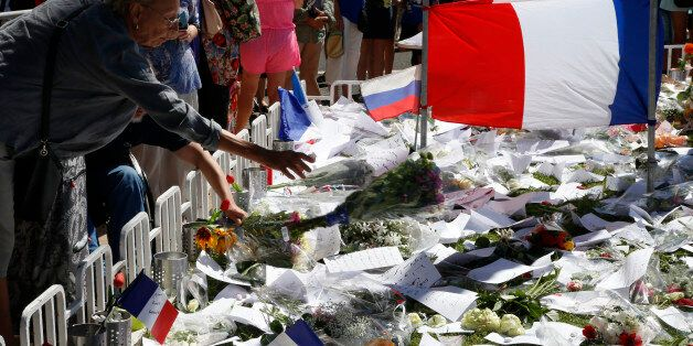 A woman adds a bouquet of flowers near French flags placed in tribute to victims, two days after an attack...