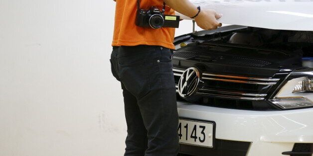 A dealer checks a Volkswagen car at a used car dealership in Seoul, South Korea, October 2, 2015. German...