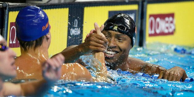 Cullen Jones, right, reacts with Caeleb Dressel, left, after their heat in the men's 50-meter freestyle...