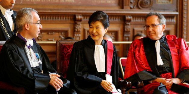 South Korean President Park Geun-hye (C) reacts after she was presented with the insignia of Doctor Honoris...