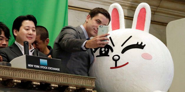 New York Stock Exchange President Tom Farley, center, takes a selfie with Line character Cony on the...