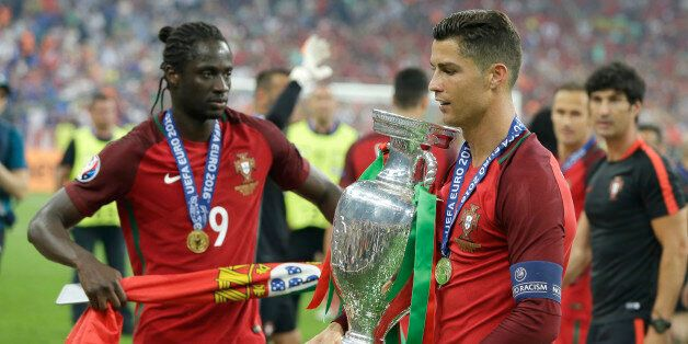 Portugal's Cristiano Ronaldo holds the trophy, next to Eder after winning the Euro 2016 final soccer...