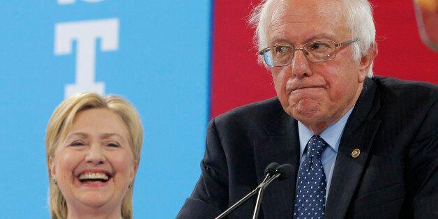 Democratic U.S. presidential candidate Hillary Clinton smiles as Senator Bernie Sanders pauses while...