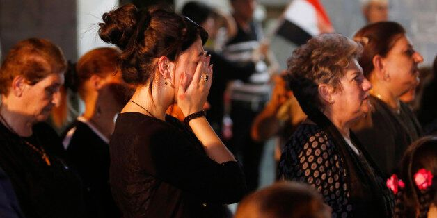 Iraqi Christians react during a mass for the victims of Sunday's truck bomb attack in Karada neighborhood...
