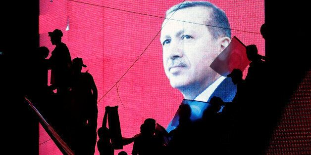 Turkish Supporters are silhouetted against a screan showing President Tayyip Erdogan during a pro-government...