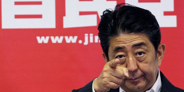 Japanese Prime Minister and leader of the ruling Liberal Democratic Party, Shinzo Abe, points a reporter...
