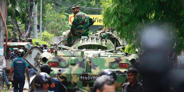 Bangladeshi soldiers and security personnel sit on top of armored vehicles as they cordon off an area...